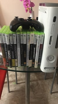 white Xbox 360 console with games and wireless controller