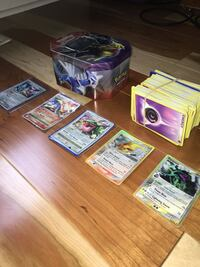 Assorted Pokémon trading cards and tin container