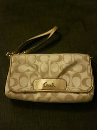 white and brown Coach leather wristlet