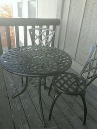 round black metal table with two chairs West Jordan