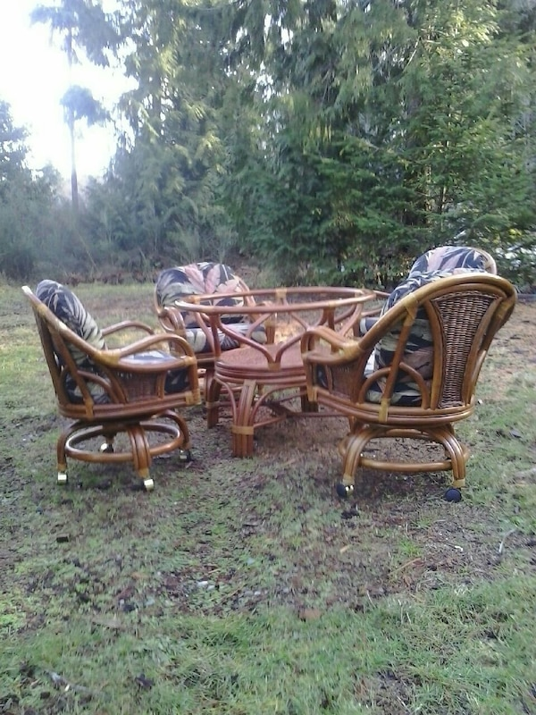round brown rattan table with four rattan rolling armchairs