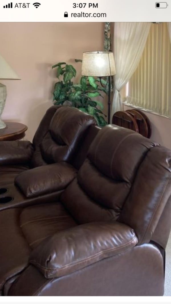 Brown 2 seater leather couch recliner. Storage with cup holders. 06b30785-ffe2-4c40-86b8-402a53b94a35