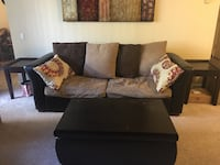 Black and brown sofa bed, loveseat, coffee table and side tables