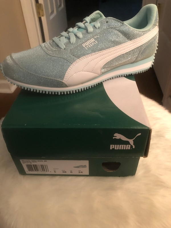 pair of gray Puma low top sneakers on box