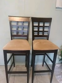 two brown wooden chairs with black leather pads 2051 mi