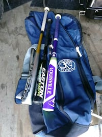 three assorted-color baseball bats and one duffel