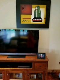 flat screen television with brown wooden TV stand Loveland, 80538