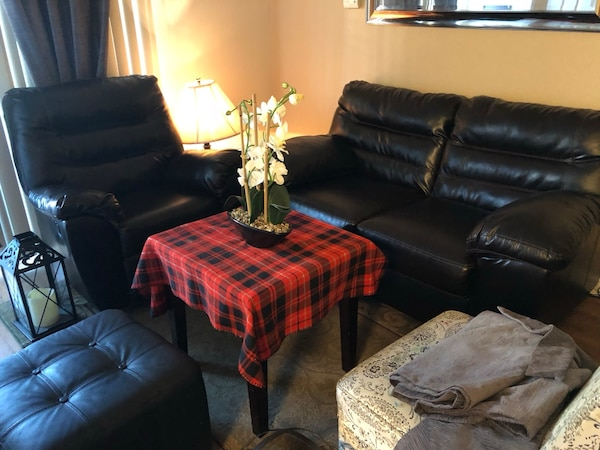 Black leather sofa set with carpet and center table, reclining chair
