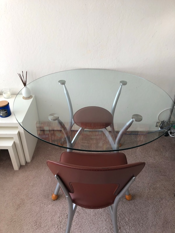 Glass circular kitchen table with matching chairs.