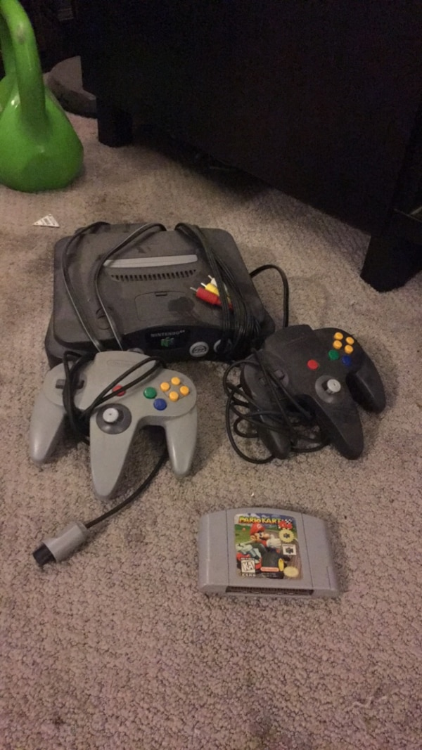 Black nintendo 64 console with controllers and game cartridges