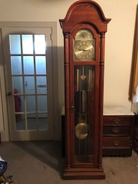Brown wood-framed grandfathers clock