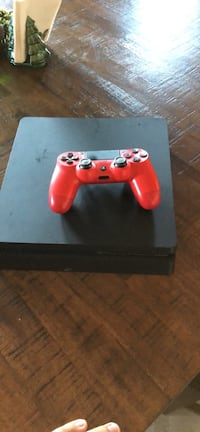 black Sony PS4 with red DualShock 4 1965 mi