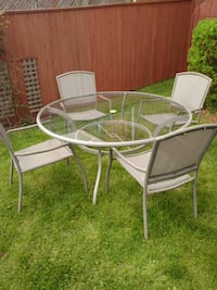 round clear glass top table with four chairs patio Hamilton, L0R 2H5