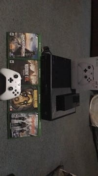Black xbox one console with white wireless controller and game cases