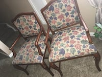 two brown wooden framed floral padded armchairs