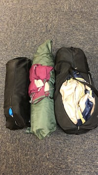 several beige and green duffel bags