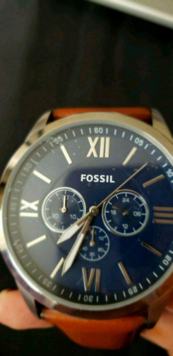 round blue chronograph watch with brown leathers