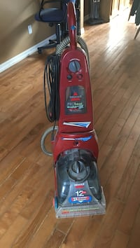 Red and black Bissell upright vacuum cleaner Kitchener, N2N 2V7