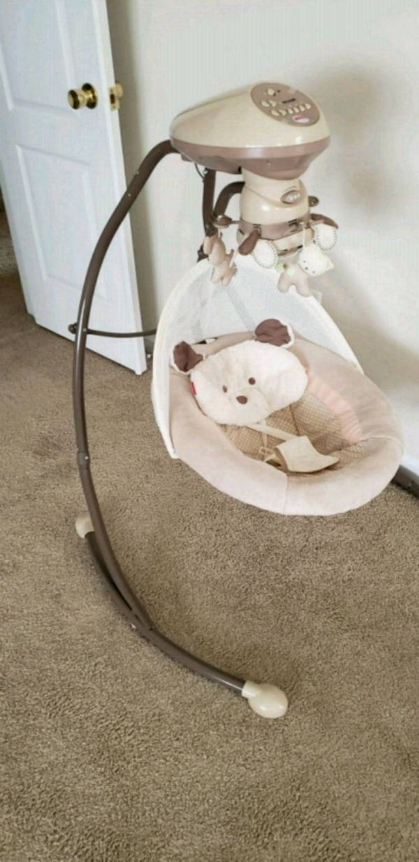 baby's white and brown cradle and swing