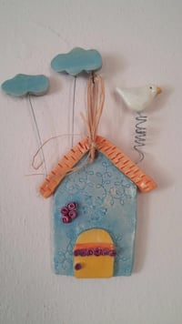 ceramic blue house with blue clouds and a white bird