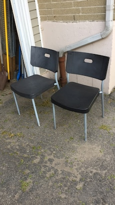 two black plastic chairs with gray steel base