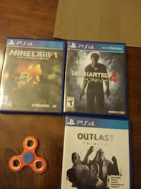 three Sony PS4 game cases and orange fidget spinner