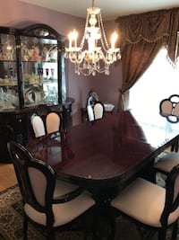 Oval brown wooden dining table with white padded chairs 6 and china