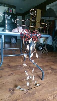 brass, gray and red floral wrought metal rack