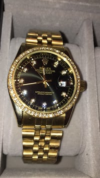 round gold-colored Rolex analog watch with link bracelet
