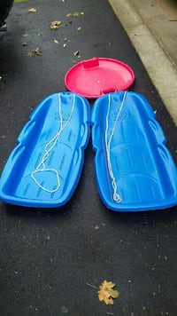 two blue and one red snow sleds