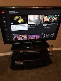 black flat screen TV with black wooden TV stand Colorado Springs, 80916