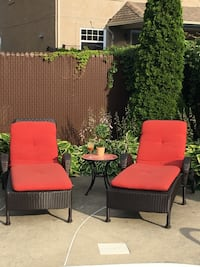 two black wicker red padded lounge chairs
