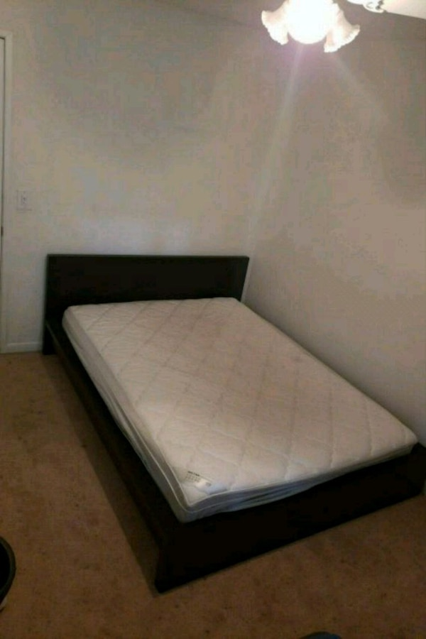 black wooden bed frame with white mattress