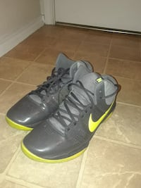 pair of black-and-yellow Nike basketball shoes