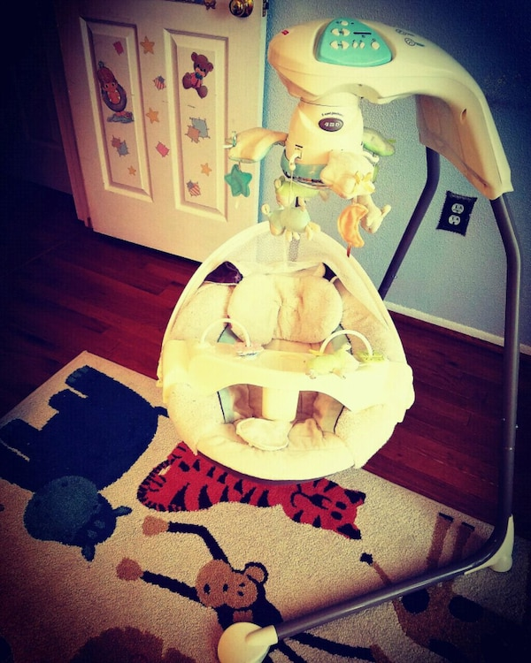 baby's white and green Fisher-Price bouncer