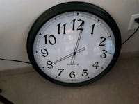 round white analog wall clock with black frame