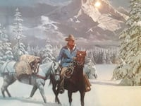 Cowboy on horseback in the snowy mountains