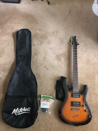 Mitchell Electric guitar with sunburst pattern, amplifier, spare strings