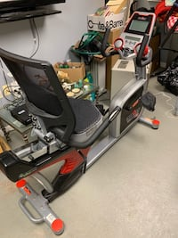 Gray and black recumbent bike with mat