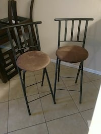 two black and brown padded chairs
