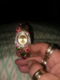 gold-colored analog watch with pink and green gemstones 96 mi