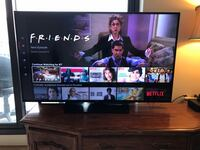 flat screen television with brown wooden TV stand 412 mi