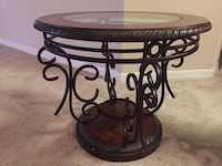 round brown wooden top table with black metal base