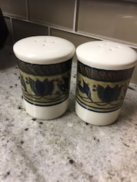two white and brown floral ceramic condiment shakers