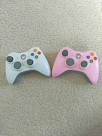 two white and purple Xbox 360 controllers