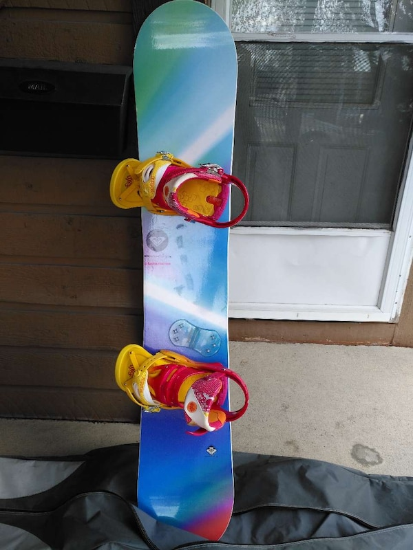 blue, green, and pink snowboard with bindings