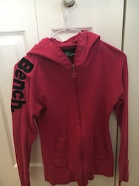 Bench Pinkish, Red Hoodie. Size medium but definitely fits like a small. Thumb Holes. Good Used condition Cochrane, T4C 1K6