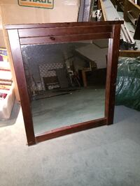 brown wooden framed wall mirror The Village
