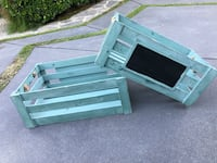 Two rustic teal painted wood crates with chalkboard and rope handles