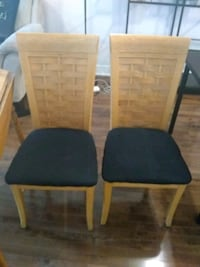 two brown wooden framed black padded chairs